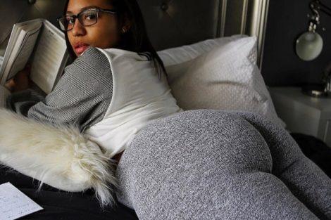 Jeune femme ronde métisse allongée et habillée montre son cul